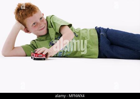Young boy with red hair and freckles age 7, playing with a toy car. Model released. Studio shot.       Ref: CRB538_103609_0043  COMPULSORY CREDIT: Mar - Stock Image