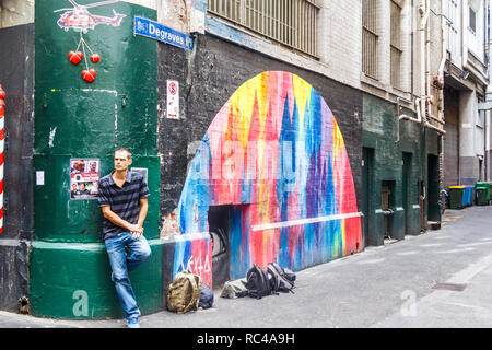 Melbourne, Australia - 21st February 2018: A man leaning against a wall by a painted mural. The lanes are famous for wall art - Stock Image