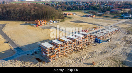 Wolfsburg, Germany, January 3., 2019: Aerial view of the shell of a large terraced house in a new development area next to an old village centre - Stock Image