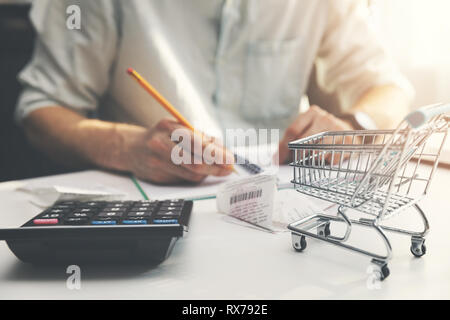 family budget planning - man counting and checking household daily expenses - Stock Image