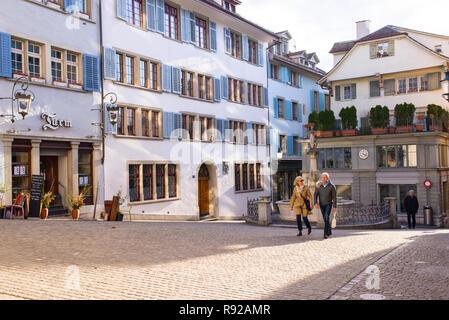 Zurich, Switzerland - March 2017: Old Couple walking in Spiegelgasse, a narrow street in the Old Town of Zurich, Switzerland - Stock Image