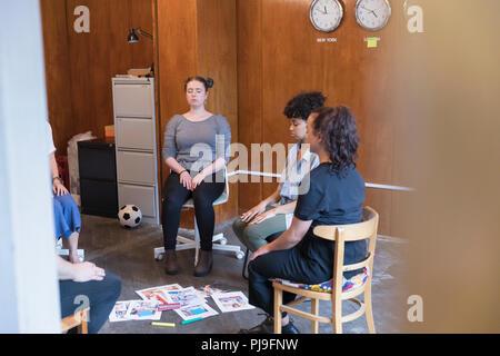 Serene, creative businesswomen meditating in circle, taking a break in meeting - Stock Image