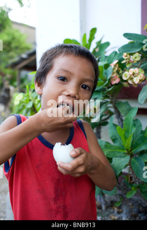 A Filipino child enjoys a balut, or cooked fertilized duck egg, in Oriental Mindoro, Philippines. - Stock Image