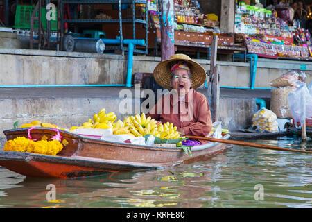 Damnoen Saduak, Thailand - August 29, 2018: Woman selling baby bananas from a boat in Damnoen Saduak Floating Market, Ratchaburi, Thailand. - Stock Image