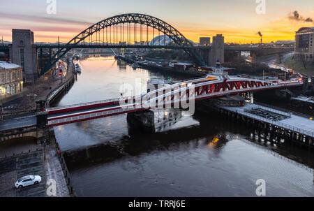 Newcastle, England, UK - February 5, 2019: The sun rises behind the iconic Tyne Bridge and swing bridge between Newcastle and Gateshead on the River T - Stock Image