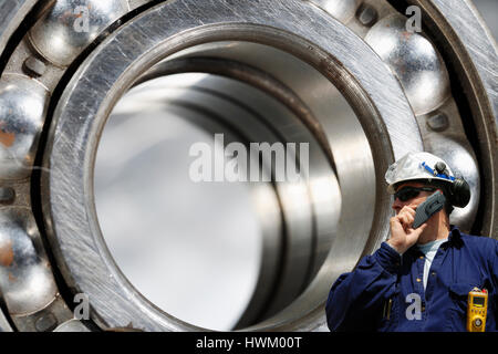 engineer, industry worker with giant ball-bearings and gears, engineering concept - Stock Image