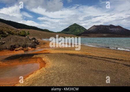Bright orange residue lies around the hot water spring at the foot of Tavurvur volcano - Stock Image