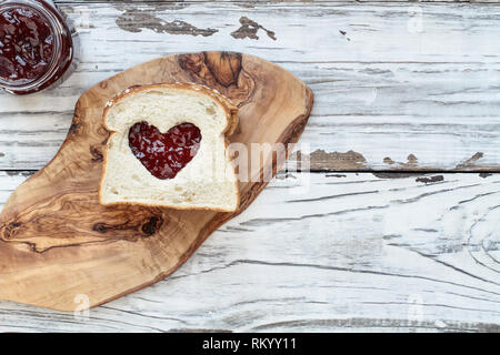 Top view of homemade peanut butter and jelly sandwich over a cutting board on a white rustic white wooden table / background with cut out heart center - Stock Image