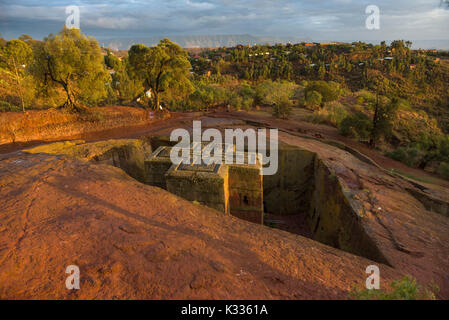 Golden sunset light coming under storm clouds and catching the top of the ancient stone-carved Bet Giyorgis (Church of St. George), Lalibela, Ethiopia - Stock Image