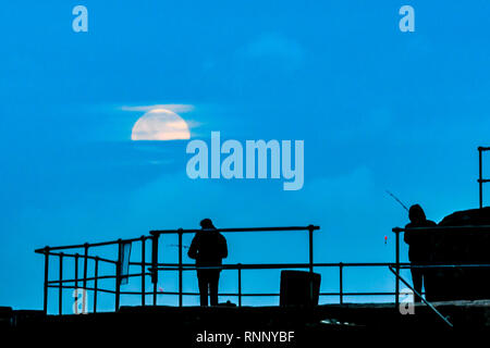 Mousehole, Cornwall, UK. 19th Feb 2019. UK Weather.  The 'super snow moon' rising above fisherman on the harbour wall at Mousehole this evening. Credit: Simon Maycock/Alamy Live News - Stock Image