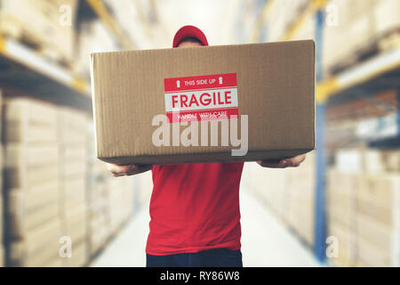 logistics warehouse worker holding package with fragile items - Stock Image