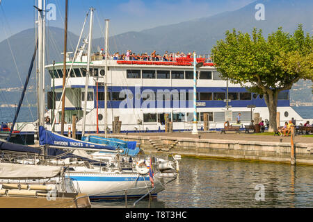 TORRI DEL BENACO, LAKE GARDA, ITALY - SEPTEMBER 2018: Sailing boats in the harbour in the town of Torri del Benaco on Lake Garda. A passenger ferry is - Stock Image