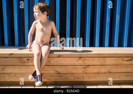 3 years child boy warming up under sun after swimming. He is sitting on footbridge entry - Stock Image