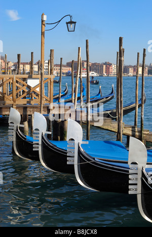 The prows of four gondolas moored in a line at a pier on the lagoon near St Mark's Square, Venice. - Stock Image