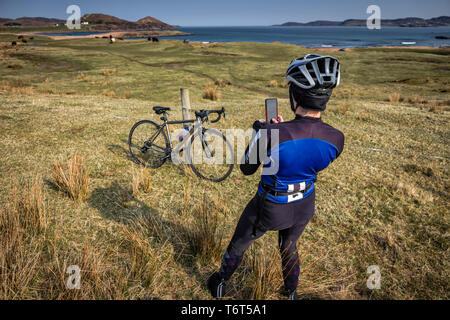 Female cyclist captures the beauty of the landscape along Loch Ewe, Poolewe, west coast of Scotland, UK. - Stock Image