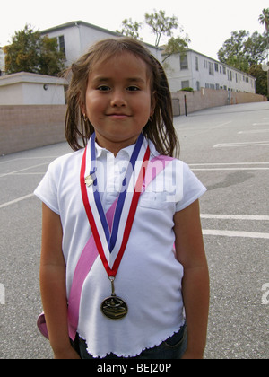 Girl wearing medal on school grounds - Stock Image