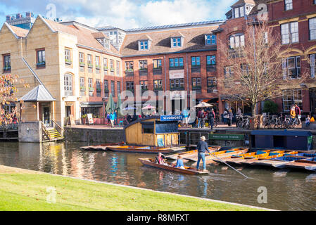 Cambridge, UK -  October 2018. Scudamore's Quayside Punting Station with tourists punting on the river Cam, view from with Magdalene College garden. - Stock Image