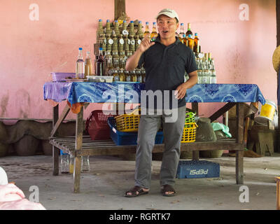 Laotian man giving a talk to visiting tourists about the distliing and selling of locally made rice whiskey  Ban Xiang Hai Laos Asia - Stock Image