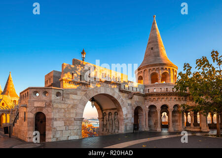 Budapest, Hungary - Entrance and tower of the famous Fisherman's Bastion on a golden autumn sunrise with Parliament of Hungary at the background and c - Stock Image