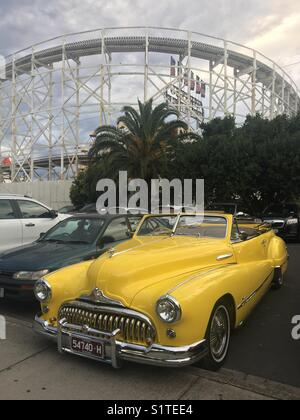 Vintage Buick restored to perfection in parking lot with old wooden roller coaster in background - Stock Image