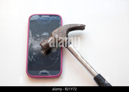 Hammer has been taken to a cell phone and cracked it - Stock Image