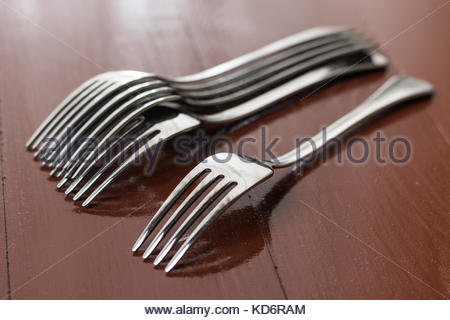 Brand new metal forks on the brown wooden table. - Stock Image