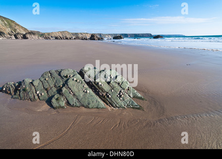Deserted pristine beach at Marloes in Pembrokeshire at low tide with a rock outcrop in the foreground on a sunny day. - Stock Image