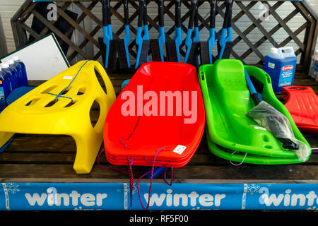 In a Garden Centre in a cold day in January a display of things useful in winter snow including three different kinds of sledge - Stock Image
