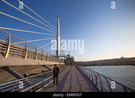 A man walking across the Golden Horn Metro bridge in Istanbul Turkey - Stock Image
