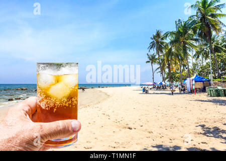 Hand holding a rum and coke cocktail in glass with ice on Hua Hin beach, Thailand - Stock Image