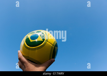 Man holding football in sky for Brazil World Cup 2014. - Stock Image