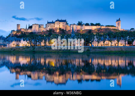 Chinon, France. Picturesque dusk view of the River Vienne at Chinon, with the floodlit Forteresse Royal and Fort Saint George in the background. - Stock Image