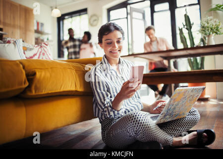 Smiling young woman using laptop and texting with smart phone on living room floor - Stock Image