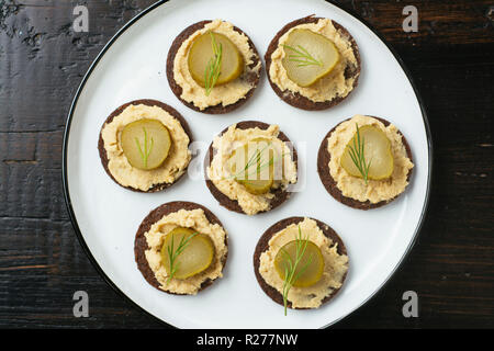 Pumpernickel rounds with hummus and pickled cucumber slices as snack. - Stock Image