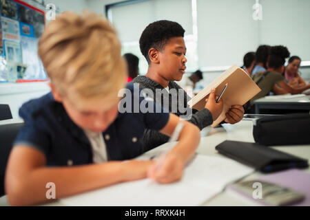 Junior high school boy opening notebook at desk in classroom - Stock Image