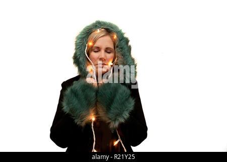 Model in beautiful coat with fancy trim has holiday lights wrapped around and eyes closed, dreaming - Stock Image