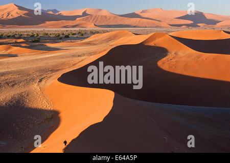 Man climbing sand dunes, Namib Naukluft National Park, Namibia - Stock Image