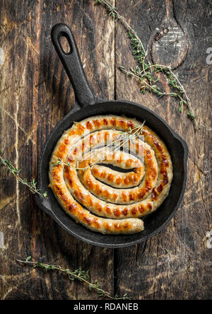 Roast sausage in a pan with thyme. On a wooden background. - Stock Image