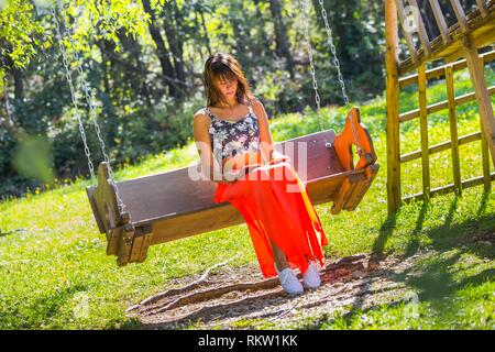 Pastoral scenery countrygirl reading book sitting on wooden bench in park - Stock Image