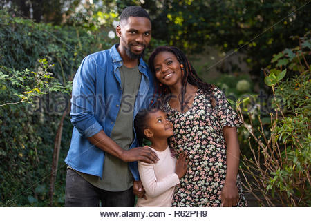 A mother, father and daughter hugging each other in a garden - Stock Image