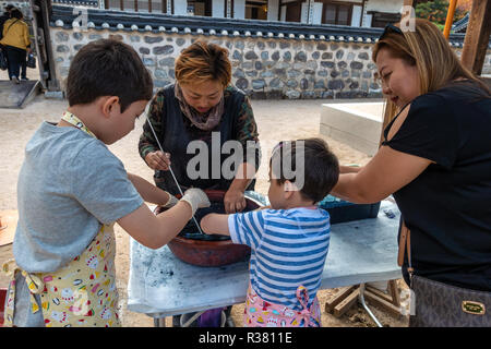 Children tie  dying under the supervision of an instructor and their mum at Namsangol Hanok Village, Seoul, South Korea - Stock Image