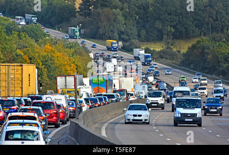 Rush hour on M25 UK motorway queue of cars trucks & lorries in traffic jam in hilly rural countryside section of London orbital highway England UK - Stock Image