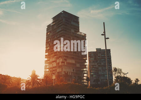 Dramatic red scenery of two residential houses with street lantern and palms in front, Barcelona district Forum, - Stock Image