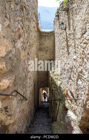Man climbing a steep stone built stairs in the old section of Limone, Italy. - Stock Image