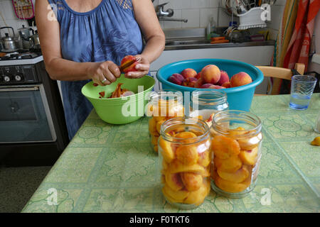 Domestic production of compote of peaches. - Stock Image