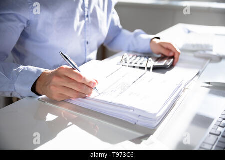 Businessperson Calculating Invoice Using Calculator At Desk - Stock Image