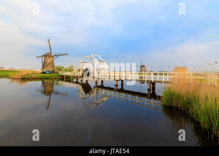 Traditional windmills and bridge on the canal framed by sunrise, Kinderdijk, UNESCO, Molenwaard, South Holland, The Netherlands - Stock Image