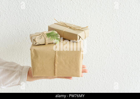 Young woman holds on stretched hand gift boxes wrapped in craft paper tied with twine. White background pastel colors. Christmas New Years presents co - Stock Image