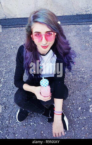 Happy beautiful teen with pink sunglasses drinks and enjoys a pink beverage sitting on urban ground - Stock Image