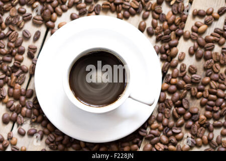 Arrangement of coffee beans and coffee cup on old wooden table. - Stock Image